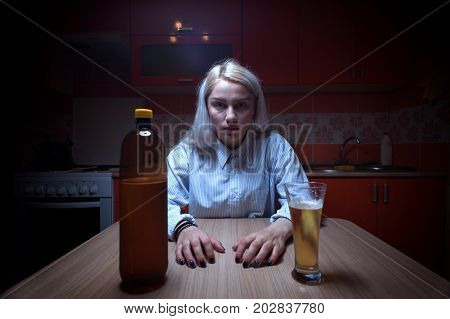 Portrait of young blonde woman sitting at the kitchen and drinking beer. Alcoholic addiction.