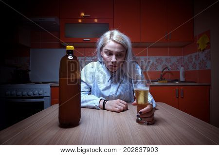 Sad depressed blonde female sitting at home and drinking beer. Young woman having troubles with alcohol.