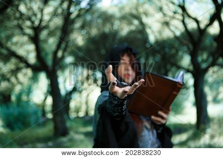 Photo of witch with outstretched hand and book