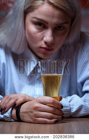 Portrait of young blonde woman sitting at home and drinking beer. Female alcohol addiction.
