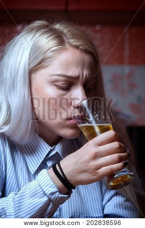 Sad depressed female drinking beer alone at home. Young woman having troubles with alcohol. Alcoholic addiction