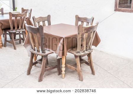Country-style wooden dining table with leather tablecloth