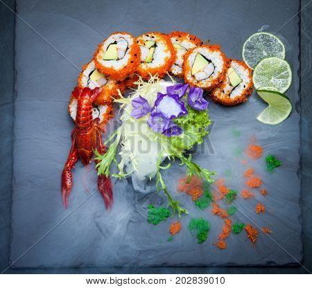 Sea crawfish and sushi on a slate dark plate with liquid smoke
