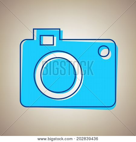 Digital camera sign. Vector. Sky blue icon with defected blue contour on beige background.