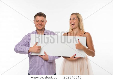 Young happy couple portrait of a confident businessman showing presentation, pointing placard gray background. Ideal for banners, registration forms, presentation, landings, presenting concept.