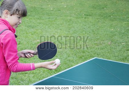 Girl playing ping pong outdoors in summer Sunny day. The emotion of anger on her face