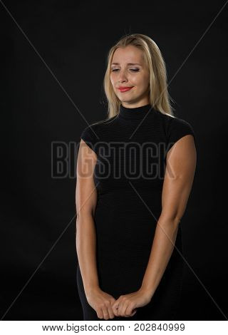 Young wistful woman portrait of a confident businesswoman showing by hands on a black background. Ideal for banners, registration forms, presentation, landings, presenting concept