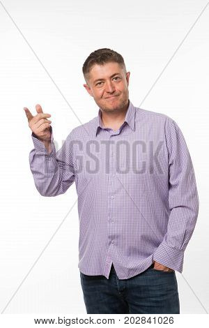 Young enigmatical man portrait of a confident businessman showing by hands on a gray background. Ideal for banners, registration forms, presentation, landings, presenting concept.