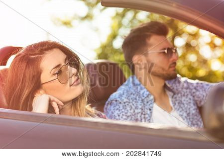 Young Couple Driving Along Country Road In Open Top Car.