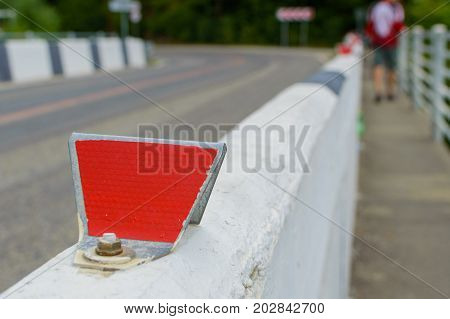 Red reflector on road. Selective focus with shallow depth of field.