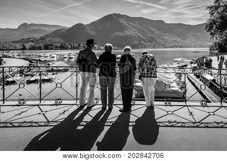 Annecy France - May 25 2016: People on the Bridge of love in Annecy France. Annecy is a commune in the Haute Savoie department of the Rhone-Alpes region in south-eastern France. Black and white photography.