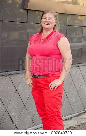 Portrait of an obese woman with blonde hair in red jeans with a big belly in a city in summer