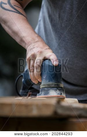 Man Is Sanding A Wooden Plank