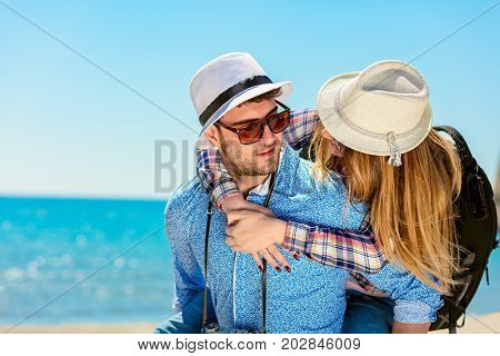 Happy man carrying his girlfriend on a piggyback ride both smiling and looking very happy enjoying their vacation.