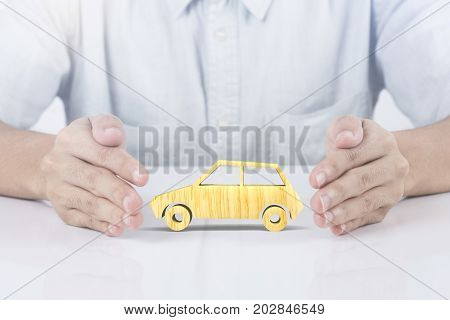 hand holding wood car insurance. concept accident prevention coverage.