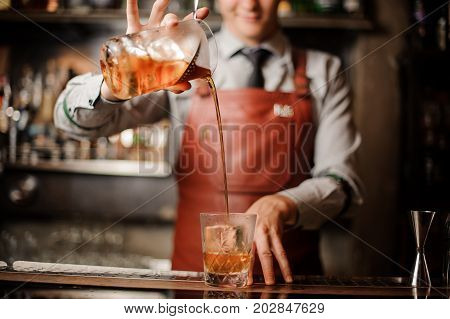 Barman in bar interior making alcohol cocktail. Professional bartender pours a drink with a strainer