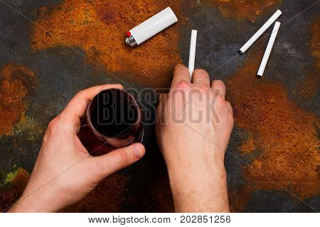 Man holding cigarette and glass of red wine in his hands. Bad unhealthy habits or new year resolution concept. Copy space