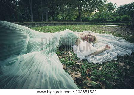 beautiful bridal portrait lie in grass with veil around her summer day