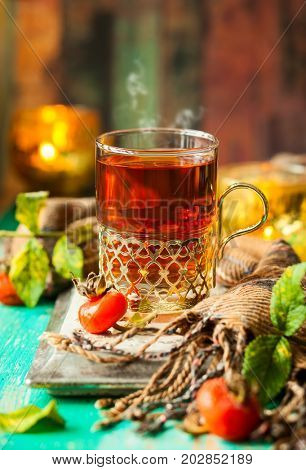 Glass of rosehip tea in a silver glass-holder and fresh berries