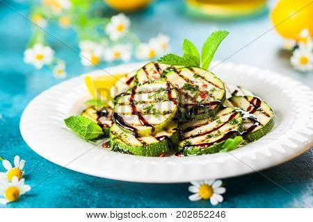 Food concept for a healthy eating summer: grilled zucchini with herbs dressing, balsamic sauce and olive oil. Soft focus