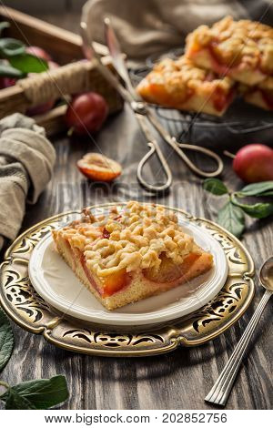 Piece of plum pie with crumble. Autumn crumb cake on old wooden table. Retro style toned.