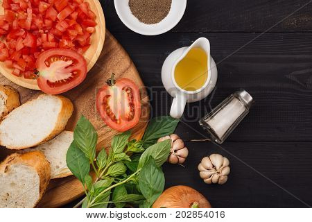 Preparing delicious Italian tomato bruschetta with chopped vegetables herbs and oil