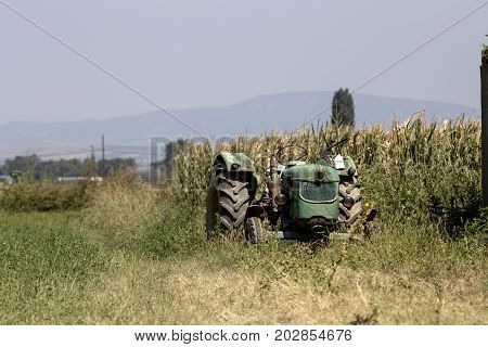 An old tractor parked on a plowed field on a sunny day