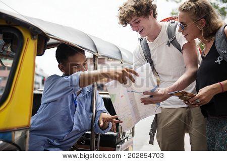 Tourists couple asking tuk tuk native taxi driver for direction