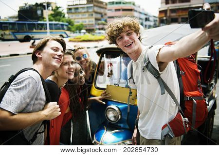 Group of caucasian tourists taking selfie infront of Tuk Tuk