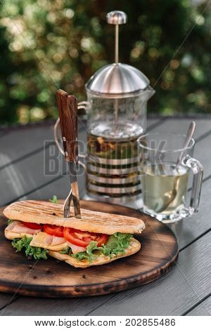Сiabatta sandwich and French press with tea on dark wooden background