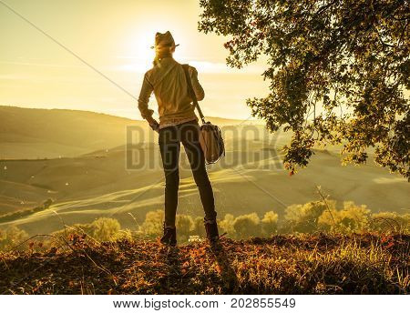 Active Woman Hiker In Hat With Bag Enjoying Sunset In Tuscany