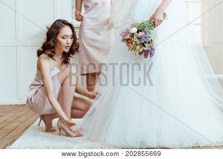 Bridesmaid Preparing Bride For Ceremony
