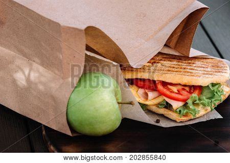 Ciabatta sandwich and apple are in a paper bag as a takeaway breakfast on dark wooden background