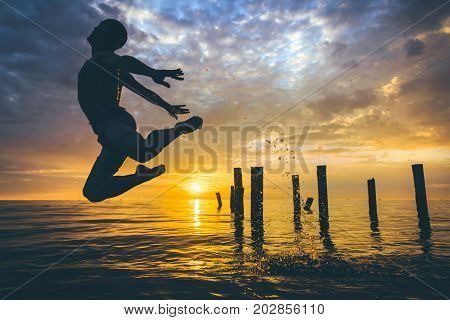 silhouette of a dancer jumping over the water