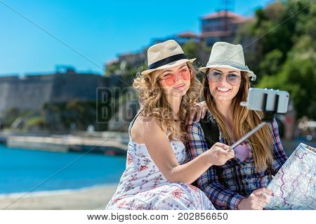 Two smiling young women sitting on a city bench making faces while taking self portraits together with a smartphone and selfie stick.