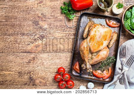 Roasted whole chicken with a golden crust with vegetables on a wooden background, top view