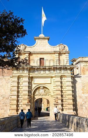 MDINA, MALTA - MARCH 29, 2017 - Tourists crossing the town gate footbridge leading to the city centre Mdina Malta Europe, March 29, 2017.