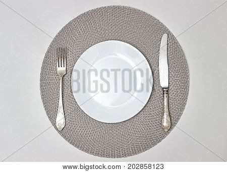 Empty plate on a gray napkin. Empty plate and cutlery. Silverware and a white plate. A white saucer on a knitted napkin. Plate fork and knife.