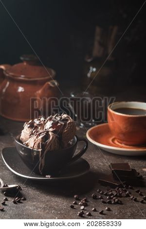 Chocolate coffee ice cream balls in a bowl over dark background