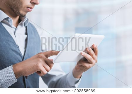 Thoughtful male person looking to the digital tablet screen, experienced entrepreneur reading some text or electronic book at the office.