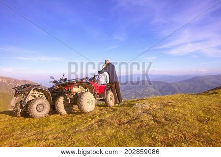 Rear view of young pair near atv. Man is showing something in distance to her girlfriend. Blurred autumn landscape mighty mountains and forests on background