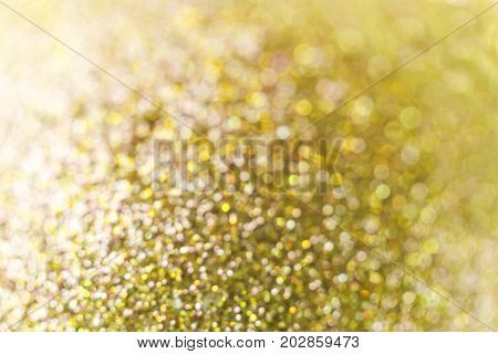 Gold Festive Christmas background. Abstract twinkled bright background with bokeh defocused lights