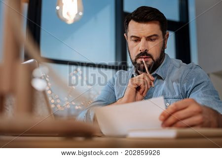 New project. Serious thoughtful professional designer looking at the scheme and biting his pencil while thinking about his project