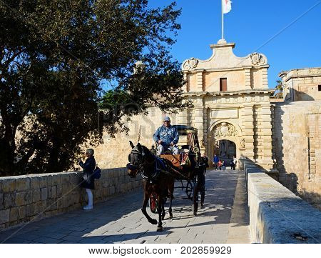 MDINA, MALTA - MARCH 29, 2017 - Horse and carriage crossing the town gate footbridge Mdina Malta Europe, March 29, 2017.