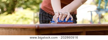 Woman Is Sanding By Hand