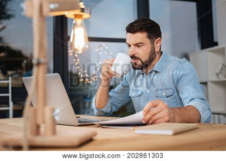 Tea time. Nice pleasant hard working businessman looking at the laptop screen and having tea while doing his job