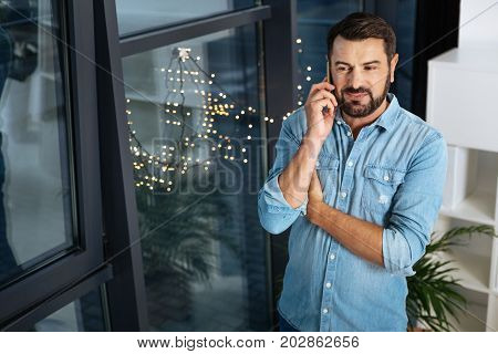 On the phone. Positive nice handsome man listening to his interlocutor and enjoying his phone conversation while standing near the window