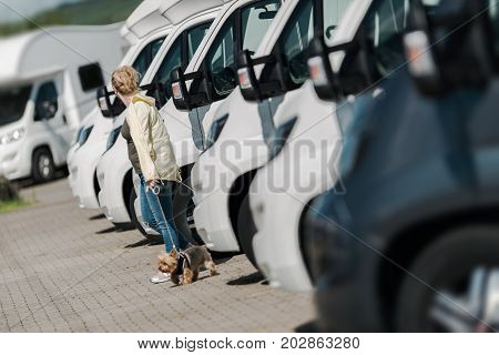 Caucasian Woman Buying New Camper Van. Looking Around To Find the Perfect Camper on the Dealership Lot.