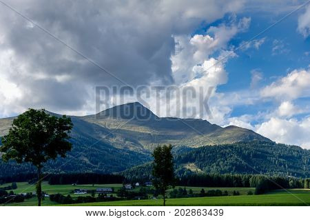 mountain view with clouds and trees in the foreground