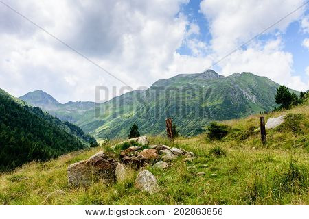 Stones in front of the mountains in the grass